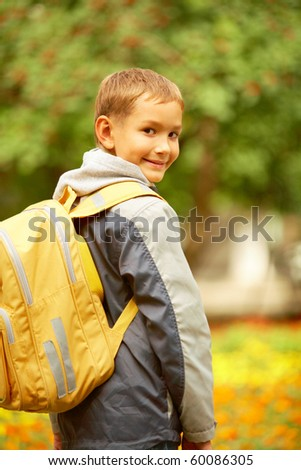 Portrait of happy lad with rucksack on back looking at camera on his way to school