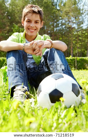 Portrait of happy lads with ball near by looking at camera