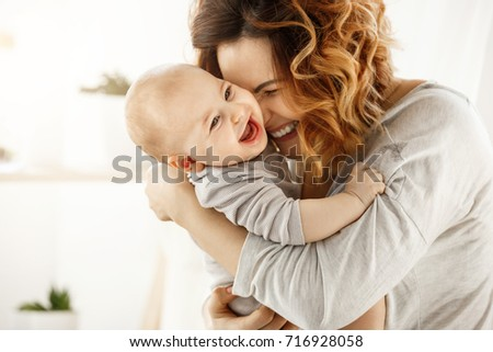 Portrait of happy laughing baby hugging with cheerful young smiling mother. Scene of pure love and happiness. Family, motherhood and lifestyle concept.