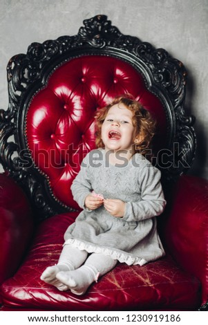 Stock Photo Portrait of happy laughing girl with red curly hair in grey dress and tights sitting on red leather arm-chair.
