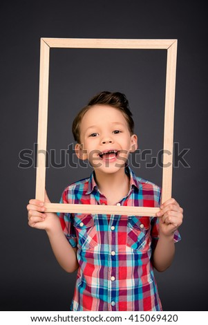 Portrait of happy laughing little boy with wooden frame
