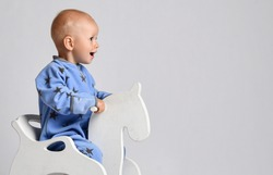 Portrait of happy laughing screaming baby boy in blue fleece jumpsuit with stars riding white kids rocking horse toy and looking at copy space. Side view