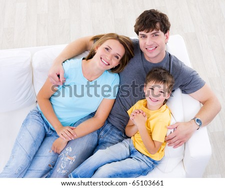 Portrait of happy laughing young family with son in casuals on the sofa at home - high angle
