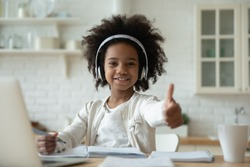 Portrait of happy little African American girl pupil in headphones study online using laptop at home, smiling small biracial child show thumb up recommend class or lesson, homeschooling concept