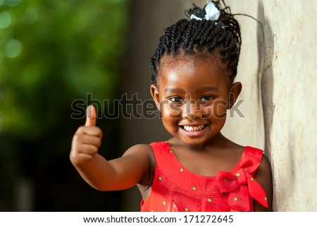 Portrait of happy little african girl doing thumbs up sign outdoors.