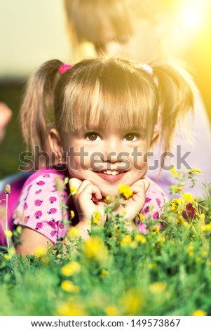 portrait of happy little baby girl on the meadow outdoor