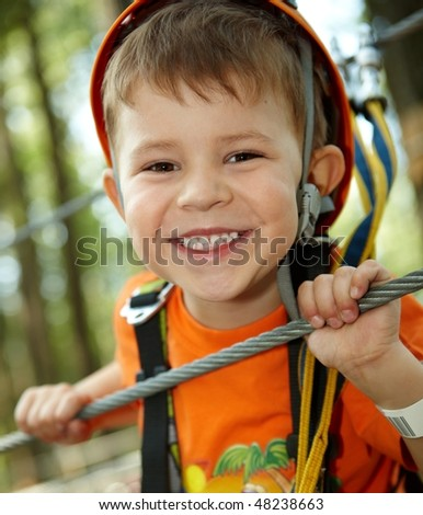 Portrait of happy little boy having fun in adventure park smiling to camera wearing mountain helmet and safety equipment.