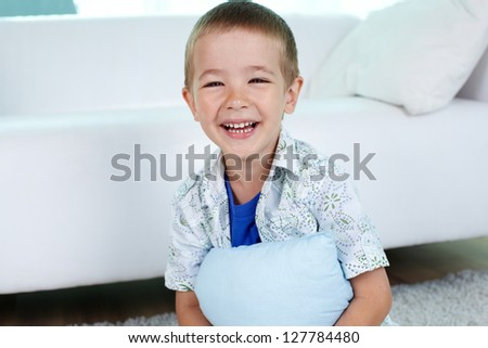 Portrait of happy little boy holding pillow
