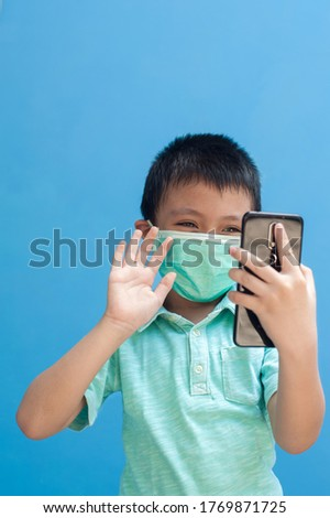 portrait of happy little boy wearing mask gesturing hi hello with his right hand to mobile phone.child communicating with other family member on video call. isolated with blue background Foto stock ©