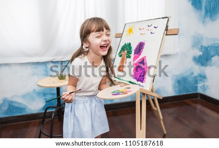 Portrait of happy little caucasian girl painting with watercolor in her art kindergarten classroom. Young creative gifted artist home school education learning doing activities back to school concept