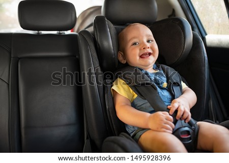 Portrait of happy little child sitting in car seat with safety belt, enjoying road trip. Cute baby boy smiling and having fun while being in the infant car seat. Toddler enjoying travel, copy space.