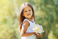 Portrait of happy little girl child with bouquet of wildflowers in sunny summer day