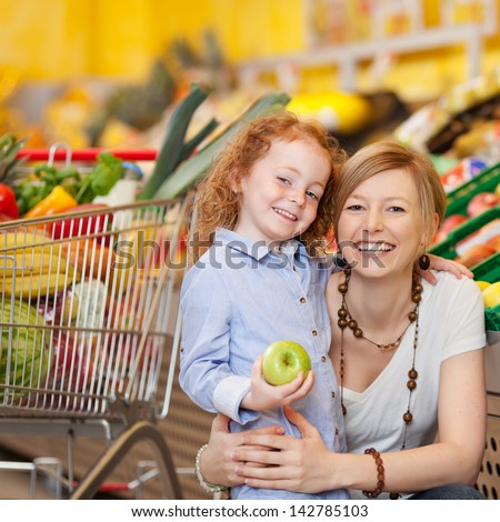 Portrait of happy little girl holding apple while mother embracing her in grocery store
