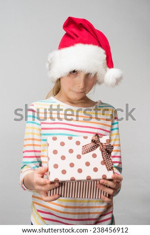Portrait of happy little girl in santa hat with gift box