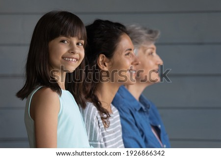 Portrait of happy little Hispanic 7s girl child look at camera smiling, mom and grandmother on background look in distance. Growing generation or small Latino kid with mother and senior grandparent.