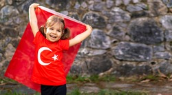 Portrait of happy little kid. Cute baby with Turkish flag t-shirt. Toddler hold Turkish flag in hand. Patriotic holiday. Adorable child celebrates national holidays. Copy space for text.