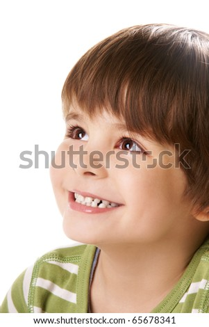Portrait of happy little smiling boy looking up on white background