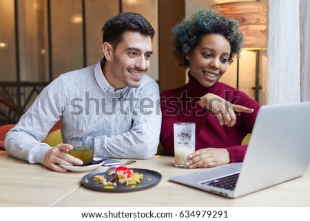 Portrait of happy lovers meeting indoors with laptop open on table in cafe. Dark-skinned girl is pointing to display with joyful smile, man is looking attentively at screen involved in what she shows.