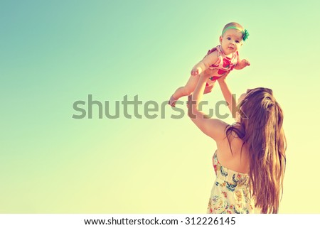 Portrait of happy loving mother and her baby outdoors. Mother and child against summer blue sky.