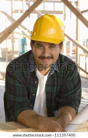 Portrait of happy male architect wearing yellow hard hat at construction site