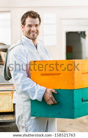 Portrait of happy male beekeeper carrying stack of honeycomb crates in beekeeping factory