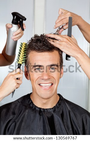 Portrait of happy male client with hairdressers styling his hair