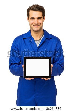 Portrait of happy male mechanic displaying digital tablet over white background. Vertical shot.