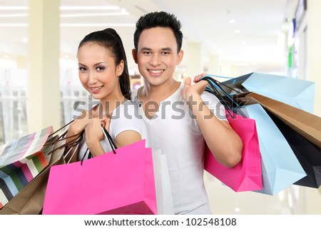 portrait of happy man and woman carrying shopping bag at the mall
