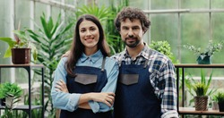 Portrait of happy man and woman in aprons standing at own small flower shop and smiling to camera after reopening. Caucasian cheerful couple entrepreneurs running own floral business. Store concept