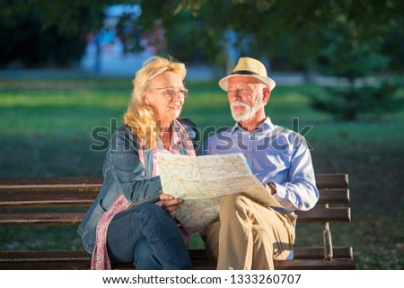 612d7f8b1cbb2 Portrait of happy man and woman reading map while sitting on a park bench.  Senior