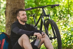 Portrait of happy man cyclist resting under tree in summer forest, holding bottle with water, enjoying view