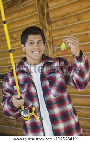 Portrait of happy man holds a fishing rod and a bait