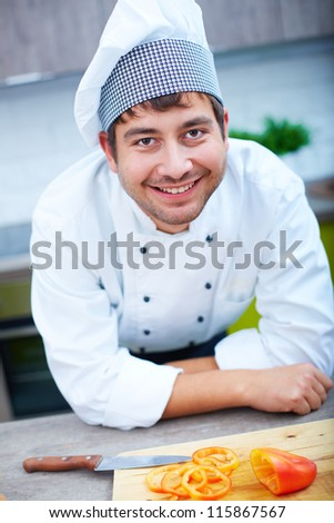 Portrait of happy man in cook uniform looking at camera