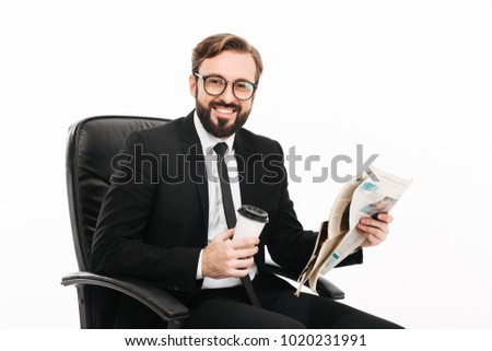 8f4a3e7feab5 Portrait of happy man in office wearing suit and eyeglasses holding  takeaway coffee and reading newspaper