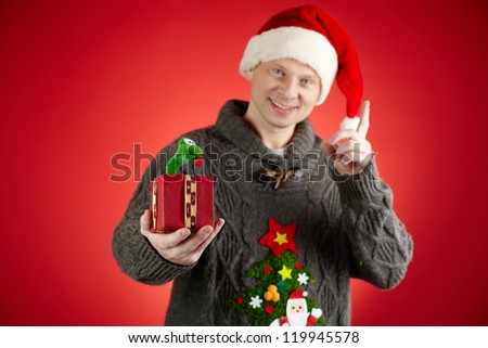 Portrait of happy man in Santa cap holding toy snake in open giftbox