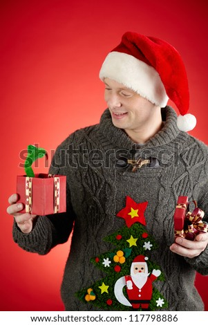 Portrait of happy man in Santa cap looking at toy snake in open giftbox