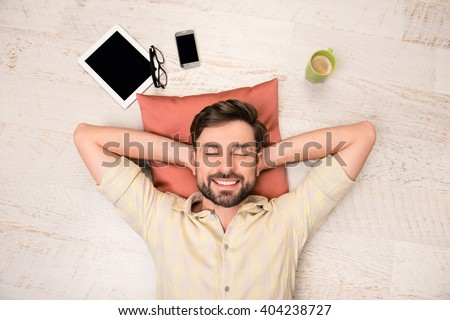 Portrait of happy man lying on floor and dreaming about smth