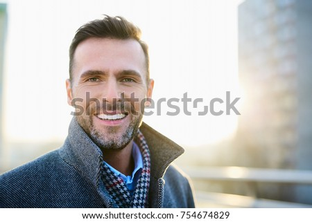 Portrait of happy man standing outdoors during sunny winter day