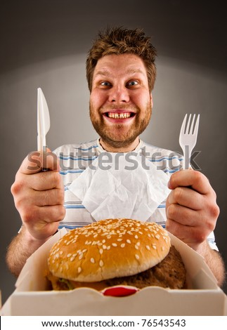 Portrait of happy man with knife and fork ready to eat burger
