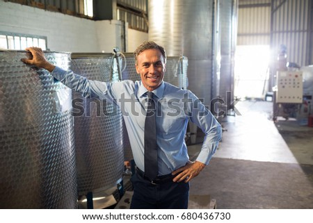 Portrait of happy manager standing near oil refinery in factory