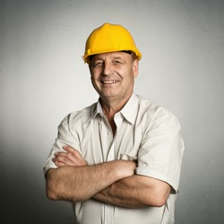Portrait of happy mature architect in helmet standing with crossed arms. Male industrial inspector of 50s wearing uniform posing in studio.