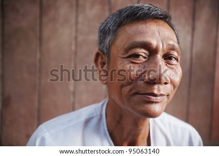 Portrait of happy mature asian man looking at camera against brown wall. Copy space