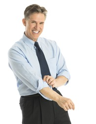 Portrait of happy mature businessman rolling up his sleeves while standing against white background