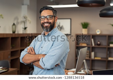 Portrait of happy mature businessman wearing spectacles and looking at camera. Multiethnic satisfied man  feeling confident in a creative office. Successful middle eastern business man smiling.