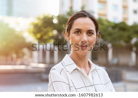 Portrait of happy mature businesswoman looking at camera. Successful proud woman in city street at sunset. Satisfied latin business woman in formal clothing smiling outdoors.