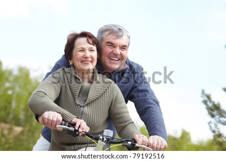 Portrait of happy mature couple on bicycle together