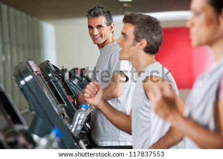 Portrait of happy mature man running on treadmill in fitness club