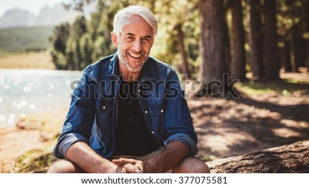 Portrait of happy mature man sitting near a lake looking at camera and smiling. Senior caucasian man sitting on a log by the lake on a summer day. #377075581
