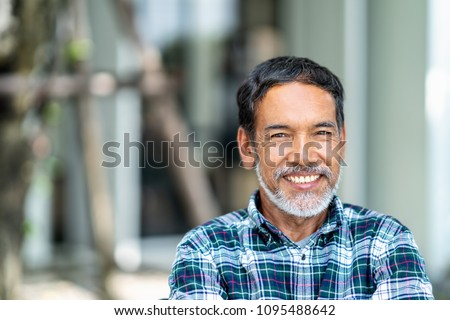 Portrait of happy mature man with white, grey stylish short beard looking at camera outdoor. Casual lifestyle of retired hispanic people or adult asian man smile with confident at coffee shop cafe.