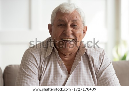 Portrait of happy mature 80s man sit on couch at home look at camera posing relaxing on weekend, smiling positive senior 70s grandfather rest on sofa at home or retirement house, show optimism